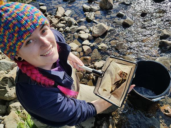 All smiles as Kacie presents a net full of Polmaddy Burn salmon fry